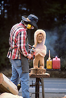 Artist sculpturing with chainsaw. Seal Rock, Oregon.