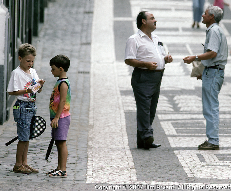 Two young boys share a candy bar, left, while their fathers talk  on a street in downtown Praia on Terceira, Azores. Far out in the Atlantic Ocean, some 850 miles off the western coast of Lisbon, Portugal lies the 425-mile long archipelago of the Azores. (Jim Bryant Photo).....