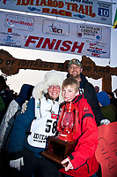 Rookie musher and red lantern award winner Celeste Davis and family pose for a photo at the finish line in Nome during the 2010 Iditarod