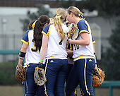 Michigan Wolverines team huddle in between innings during the season opener against the Florida Gators on February 8, 2014 at the USF Softball Stadium in Tampa, Florida.  Florida defeated Michigan 9-4 in extra innings.  (Copyright Mike Janes Photography)