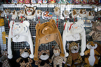 Stuffed animals and masks made with real tiger fur hang in a display for sale at the Siberian Tiger Park in Haerbin, Heilongjiang Province, China. The Siberian Tiger Park is described as a preserve to protect Siberian tigers from extinction through captive breeding.  Visitors to the park can purchase live chickens and other meat to throw to the tigers.  The Siberian tiger is also known as the Manchurian tiger..