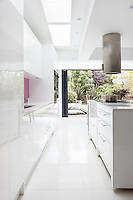 The sleek white kitchen has windows at the far end which open out onto the garden