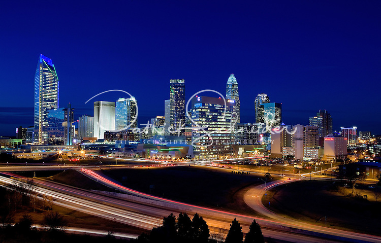 Downtown buildings in the Charlotte NC skyline take on a brilliant glow. Buildings shown in photo include the Duke Energy headquarters (far left), Wells Fargo buildings (middle), Bank of America tower (tallest on right) and Hearst Tower (tall far right).<br /> <br /> Charlotte Photographer - PatrickSchneiderPhoto.com