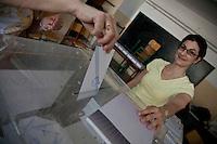 Atene,17 giugno 2012 elezioni nazionali: in un seggio una donna inserisce la scheda nell'urna, un'altra donna la osserva con la mano appoggiata sull'urna.i<br /> Athens, June 17, 2012 national elections, voting<br /> Ath&egrave;nes, Juin 17, 2012 &eacute;lections nationales, les bureaux de vote