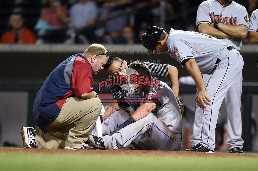 Salt River Rafters infielder Trevor Story (8) is looked at by team trainers Alan Rail and Masa Abe along with manager Andy Haines after a collision scoring a run during an Arizona Fall League game against the Mesa Solar Sox on October 18, 2014 at Cubs Park in Mesa, Arizona.  Mesa defeated Salt River 8-4.  (Mike Janes/Four Seam Images)