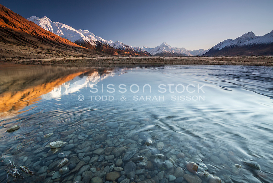 Winter sunrise looking across the Tasman River towards Aoraki / Mt Cook covered in snow, Mackenzie Country, Canterbury, New Zealand.