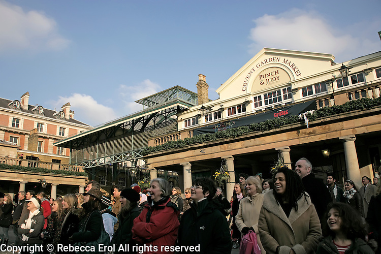 British public enjoying a performer on Covent Garden Piazza, London, UK