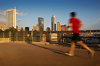 A man jogging on the Lamar Street Pedestrian Bridge overlooking the Austin Skyline in downtown