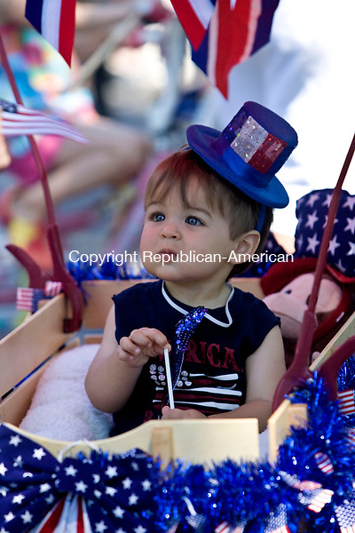 THOMASTON, CT - 04 JULY 2010 -070410JT02-<br /> Mason Demicco, 13 months, is distracted by an American flag as he rides in a wagon during the 45th annual Children's Parade, organized by Mary Reynolds, for Independence Day on Perritt Drive in Thomaston on Sunday.<br /> Josalee Thrift Republican-American