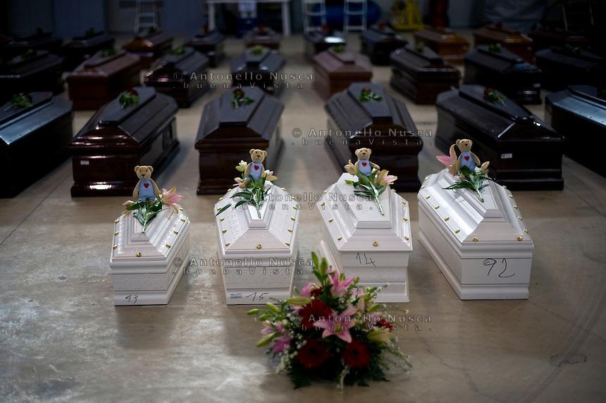 Lampedusa, 5 Ottobre, 2013. Le bare di 4 giovani vittime del tragico naufragio in cui morirono più di 300 persone, nell'hangar dell'aeroporto di Lampedusa, in attesa di venire trasferite nei vari cimiteri della Sicilia