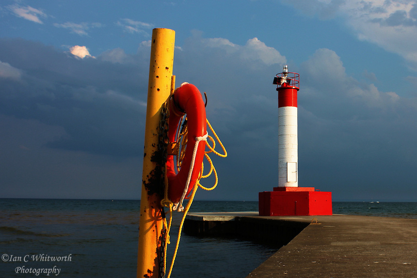 The colours of the life preserver and lighthouse stand out against a moody sky on Lake Ontario