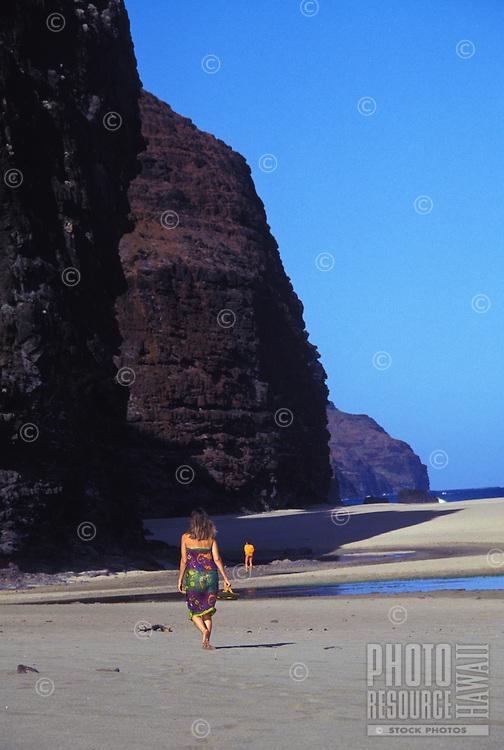 Na Pali camper walking towards cave at Kalalau beach