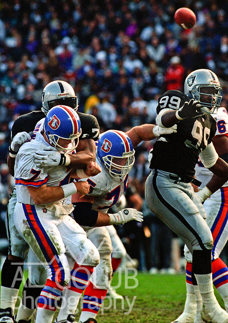 Oakland Raiders vs. Denver Broncos at Oakland Alameda County Coliseum Sunday, December 24, 1995.  Broncos beat Raiders  31-28.  Oakland Raiders defensive end Nolan Harrison (74) and linebacker Aundray Bruce (99) rush Denver Broncos quarterback John Elway (7).