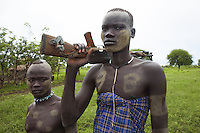 Ethiopia. Southern Nations, Nationalities, and Peoples' Region. Omo Valley. Mursi tribe. Agro-pastoralist group. Nomadic. Two Mursi men, one with a Kalashnikov on his shoulder. The AK-47 (also known as the Kalashnikov, AK, or Kalash) is a selective-fire (semi-automatic and automatic) assault rifle. The Mursi women are famed for wearing large plates in their lips (round clay plates placed into a cut in the lower lip) and ears. The disk is seen as a symbol of beauty and wealth.  The Omo Valley, situated in Africa's Great Rift Valley, is home to an estimated 200,000 indigenous peoples who have lived there for millennia. Amongst them are 8'000 Mursi who dwell between the Omo and Mago rivers. Southern Nations, Nationalities, and Peoples' Region (often abbreviated as SNNPR) is one of the nine ethnic divisions of Ethiopia. 11.11.15 © 2015 Didier Ruef