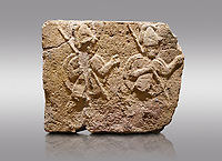 Picture &amp; image of Hittite relief sculpted orthostat stone panel of Long Wall Limestone, Karkamıs, (Kargamıs), Carchemish (Karkemish), 900-700 B.C. . Anatolian Civilisations Museum, Ankara, Turkey.<br /> <br /> Two helmeted soldiers in short skirt carry shield on their backs and spear in their hands.<br /> <br /> On a gray background.