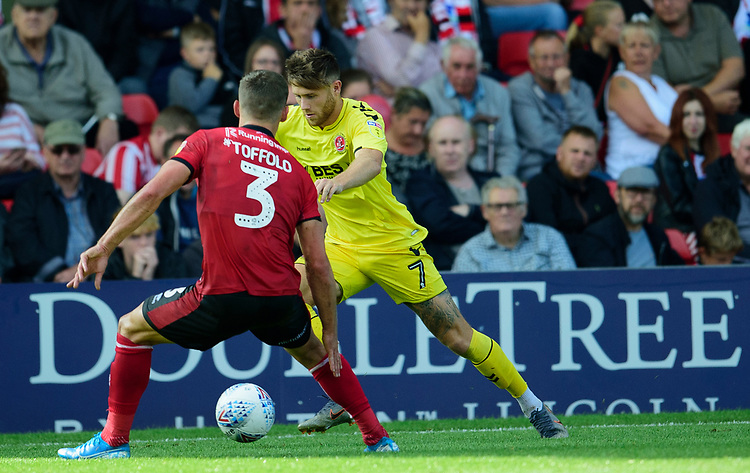 Fleetwood Town's Wes Burns vies for possession with Lincoln City's Harry Toffolo<br /> <br /> Photographer Andrew Vaughan/CameraSport<br /> <br /> The EFL Sky Bet League One - Lincoln City v Fleetwood Town - Saturday 31st August 2019 - Sincil Bank - Lincoln<br /> <br /> World Copyright © 2019 CameraSport. All rights reserved. 43 Linden Ave. Countesthorpe. Leicester. England. LE8 5PG - Tel: +44 (0) 116 277 4147 - admin@camerasport.com - www.camerasport.com