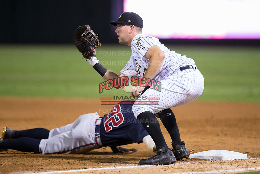 Casey Gillaspie (39) of the Charlotte Knights waits for a pick-off throw as Micah Johnson (22) of the Gwinnett Braves dives back into first base at BB&T BallPark on August 4, 2017 in Charlotte, North Carolina.  The Knights defeated the Braves 7-5 in a game shortened to 8 innings due to rain.  (Brian Westerholt/Four Seam Images)