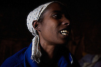 Emembet Albachew, 26 years old, HIV positive, smiles while cleaning dry peas in her home in a very poor neghborhoood in Addis Ababa, Ethiopia on Monday June 12 2006. Emembet lives with her daughter, 3 years old Magdass, her only reason to live. On June 20th she was reported to be dead by the St Paul hospital staff while she was enduring a deep physical crises. after almost 4 weeks of hospitalization she was discharged and could finally reunite with her daughter that meanwhile lived with a local home base care giver. . Ethiopia is one of the countries most affected by HIV/AIDS. Of its population of 77 million, three million are HIV-positive, according to government statistics. Every day sees 1,000 new infections. A million children under 14 have lost one or both parents to AIDS, and 200,000 children are living with AIDS. That makes Ethiopia the country with the most HIV-positive children.