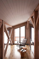 A contemporary rocking chair and a pair of solid cedarwood tables furnish the first floor landing