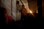 A candle provides a little light for children inside their tent at Azaz Camp, just inside the Syrian border with Turkey, Feb. 22, 2013. There is very little electricity in the camp and no running water. According to administrators, this camp holds roughly 9,000 to 10,000 internally displaced persons (IDP's). The UN Refugee Agency has reported a sharp increase in refugees fleeing Syria for neighboring countries in the first months of 2013.