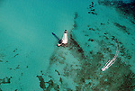 Aerial view of Alligator Light in the gem colored waters of the Atlantic off the coast of the Florida Keys with a boat motoring by