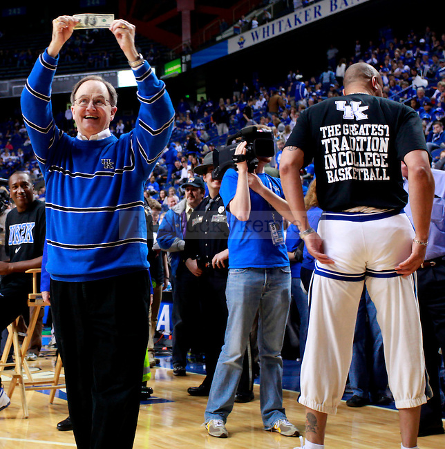 """University of Kentucky President Lee Todd holds up $100 dollars donated to the President's Scholarship Initiative after Kenny """"Sky"""" Walker fit into his old college basketball shorts during ESPN College Game Day at Rupp Arena on Saturday. Photo by Zach Brake 