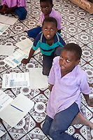 Jambiani, Zanzibar, Tanzania.  Boys in Primary School.  Students sit on the floor since the school has no furniture.  The workbook, in Swahili, is about eating foods strong in protein, to build strong bodies.