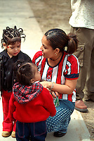 Mother age 23 with children ages 2 & 3  at Cinco de Mayo festival.  St Paul Minnesota USA