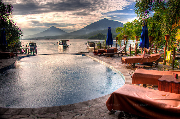 The pool at the Lembeh Resort appeals in the afternoon after a day diving in the Lembeh Strait beyond.  (The mountains in the background are North Sulawesi, Indonesia.)  (HDR image)