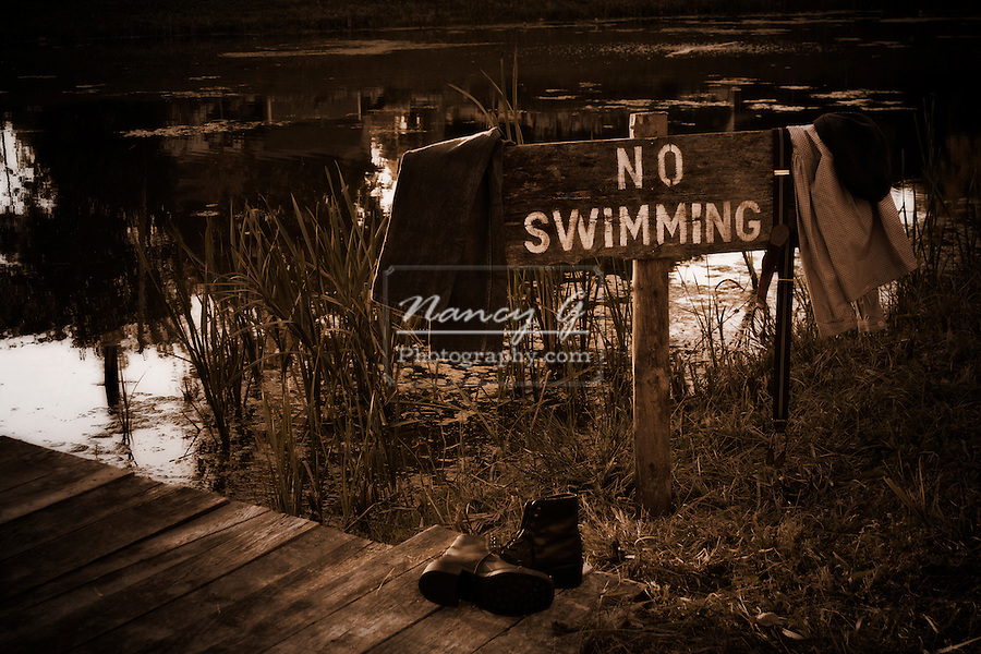 Vintage NO Swimming sign next to a pond with clothes hanging off sign