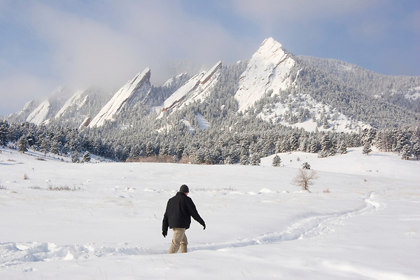 Caucasian male hiking after a snowstorm in the Rocky Mountain foothills, Chautauqua Park, Boulder, Colorado, USA
