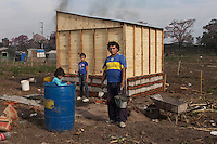 "El ""Mocho"" es albañil de profesión pero actualmente esta desempleado, ayuda a sus vecinos a construir sus casas,  junto a el posan Tiago y Aldana.As one more face of  the housing problems in Argentina, about 1,500 families invaded a large piece of land belonging to a sugar cane plantation and factory, Concepcion, in the Northern province of Tucuman. After a decade of strong economic growing, Argentina is still showing high levels of poverty and underdevolpment."