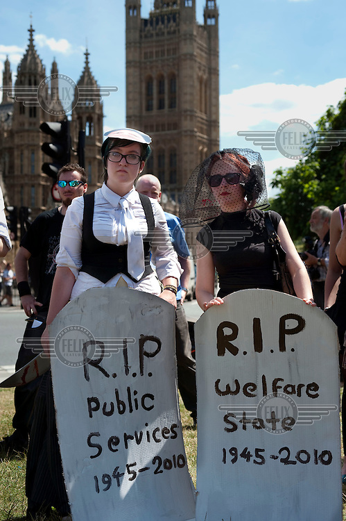 A group calling themselves 'Can't Pay Won't Pay' demonstrate against the public spending cuts imposed by the government in the Budget, outside the Houses of Parliament in Westminster, London. They hold signs reading 'R.I.P Public Services 1945-2010' and 'R.I.P Welfare State 1945-2010.'