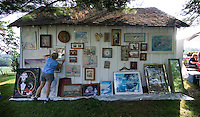 The owner of a few old paintings and artworks prices the items placed on the side of an out building  at a rural yard sale on a farm near West Liberty, Ohio.<br />