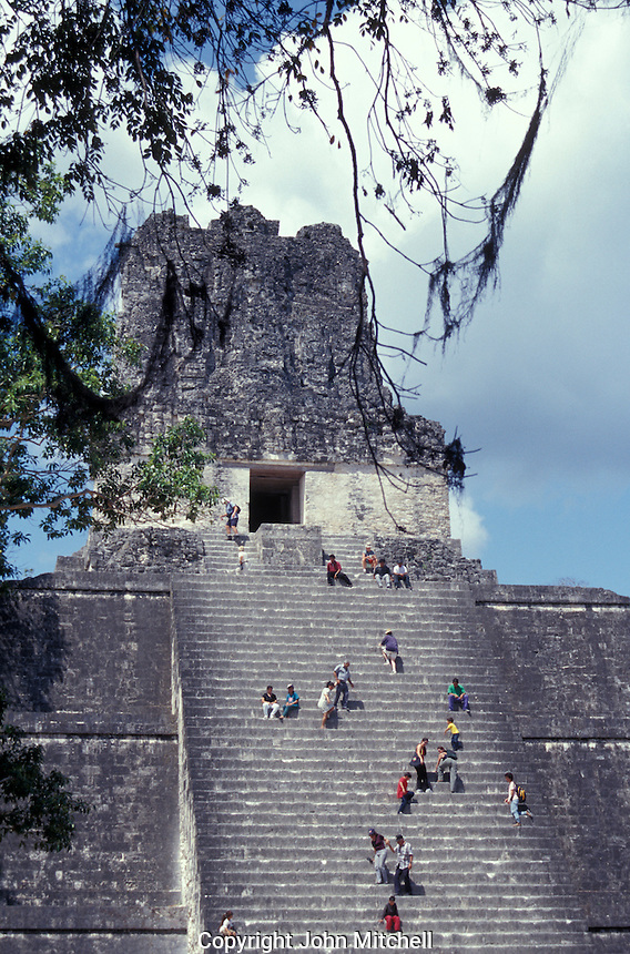 Tourists climbing Temple II, the Temple of the Maskas, at the Mayan ruins of Tikal, Guatemala