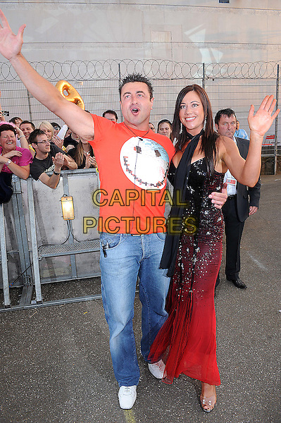 MARIO MARCONI (SHAUN) & LISA APPLETON.Housemates enter the Big Brother House for Big Brother 9, Borehamwood, England. .June 5th, 2008.arrivals full length couple red smily face t-shirt print black dress scarf sparkly jeans denim waving.CAP/BEL.©Tom Belcher/Capital Pictures.
