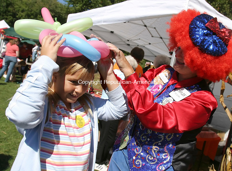 WATERTOWN,  CT 24 September 2005 -092405BZ03- Caroline Henry, 7, of Watertown, is fitted with a balloon hat by Dimples the Clown at the 2005 Fall Festival at Veteran's Memorial park Saturday.<br /> Jamison C. Bazinet / Republican-American