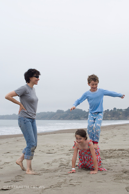 Stinson Beach, CA Nephew, six, and niece, eight, showing off acrobatic tricks for aunt on beach vacation MR