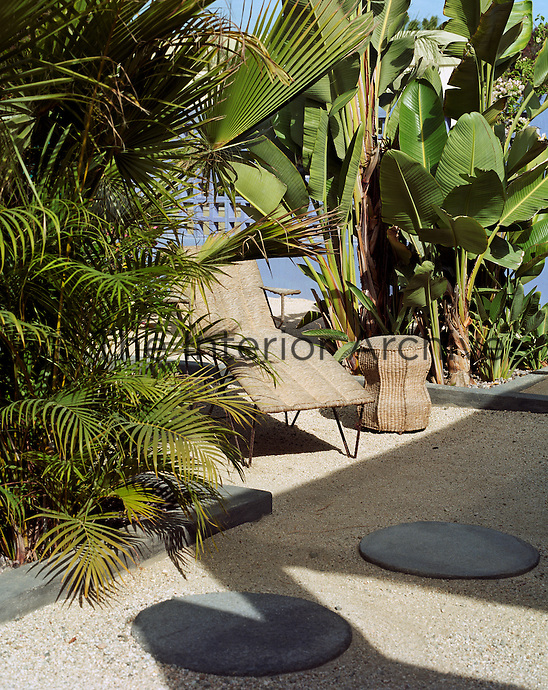A rattan sun-lounger and side table are placed in a cool spot under the spreading leaves of a banana tree