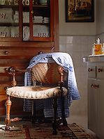 An old Indian Kilim has been used to upholster a gentleman's chair in the corner of this bathroom