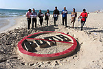 Wounded Palestinians, who were lose their legs during the clashes with Israeli troops, stand in front a sand draw during a protest calling to boycott Puma sport company, on the beach of Gaza city on May 29, 2019. Puma is the main sponsor of the Israel Football Association (IFA), which includes teams in Israel's illegal settlements on occupied Palestinian land. Photo by Mahmoud Ajjour