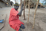 A Dinka woman digs holes to bury sticks that will form a wall in her hut in the Rhino Refugee Camp in northern Uganda. As of April 2017, the camp held almost 87,000 refugees from South Sudan, and more people were arriving daily. About 1.8 million people have fled South Sudan since civil war broke out there at the end of 2013. About 900,000 have sought refuge in Uganda.