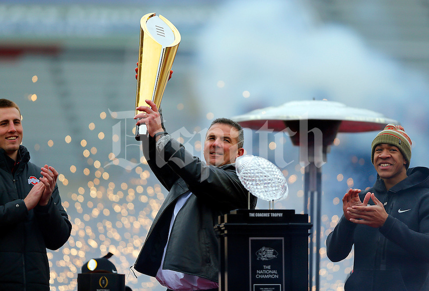 Head coach Urban Meyer holds the national championship trophy on stage with tight end Jeff Heuerman (left) and wide receiver Evan Spencer during the Ohio State football National Championship celebration at Ohio Stadium on Saturday, January 24, 2015. (Columbus Dispatch photo by Jonathan Quilter)