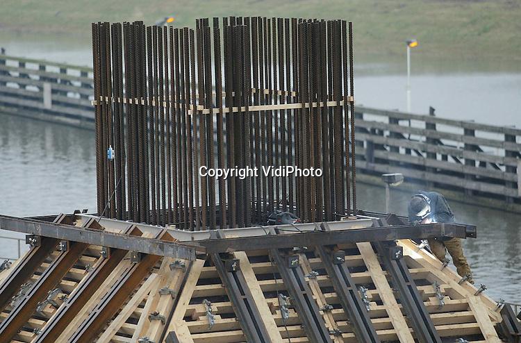 Foto: VidiPhoto..TIEL - In het Amsterdam-Rijnkanaal bij Tiel werkt de Bouwcombinatie BR4 aan twee bruggen. Pal naast de A15 komt de spoorbrug voor de Betuwelijn te liggen. Daarnaast wordt een oeververbinding voor het lokale verkeer gebouwd. De huidige verkeersbrug wordt dan afgebroken. De beide bruggen moeten 1 januari 2004 klaar zijn. Deze week wordt 's nachts het beton gestort voor de middenpijlers. De werkzaamheden worden uitgevoerd in opdracht van de Projectorganisatie Betuweroute. Foto: Lassen boven op een middenpijler.