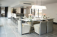 A spacious, stylish open plan room with kitchen and dining areas. Upholstered leather grey chairs are placed around a glass-topped table for six.