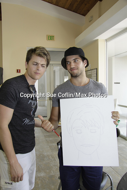 """Bryan Craig """"Morgan"""" draws his """"brother Michael"""" -Chad Duell - General Hospital  at 15th Soapfest 2014 painting party on May 24, 2104 gathered together to do paintings with guests and the proceeds went to charity - The weekend of events is held on Marco Island, Florida.  (Photo by Sue Coflin/Max Photos)"""
