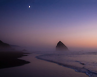 Twilight during Cannon Beach Sunset with half moon rising and waves rolling onto sandy beach