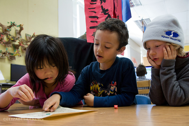 Berkeley CA Kindergarten students , one Asian, playing math game together in class