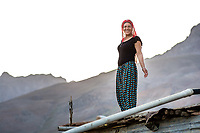 Munzur Valley, Turkey - July 15, 2014 - An Alevi woman watches the herds come in for the night from her rooftop in Kodi village.   CREDIT: Michael Benanav for The New York Times