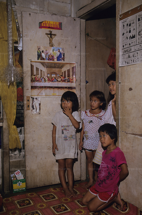 1989: Inside Kelabit native longhouse. Children near doorway with Christian religious and save the rainforest material. Long Napir, Limbang district, Sarawak, Borneo<br />